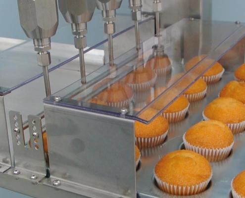 Detalle máquina inyectadora semiautomática para rellenos en pastelería.